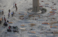 Policemen stand next to the bodies buried in shallow graves on the banks of Ganges river in Prayagraj, India, Saturday, May 15, 2021. Police are reaching out to villagers in northern India to investigate the recovery of bodies buried in shallow sand graves or washing up on the Ganges River banks, prompting speculation on social media that they were the remains of COVID-19 victims. (AP Photo/Rajesh Kumar Singh)
