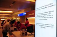 An electronic sign board in Singapore International Airport asks family members of passengers on missing AirAsia Flight QZ8501 to gather at the Relatives Holding Area, and provides contact details for further information