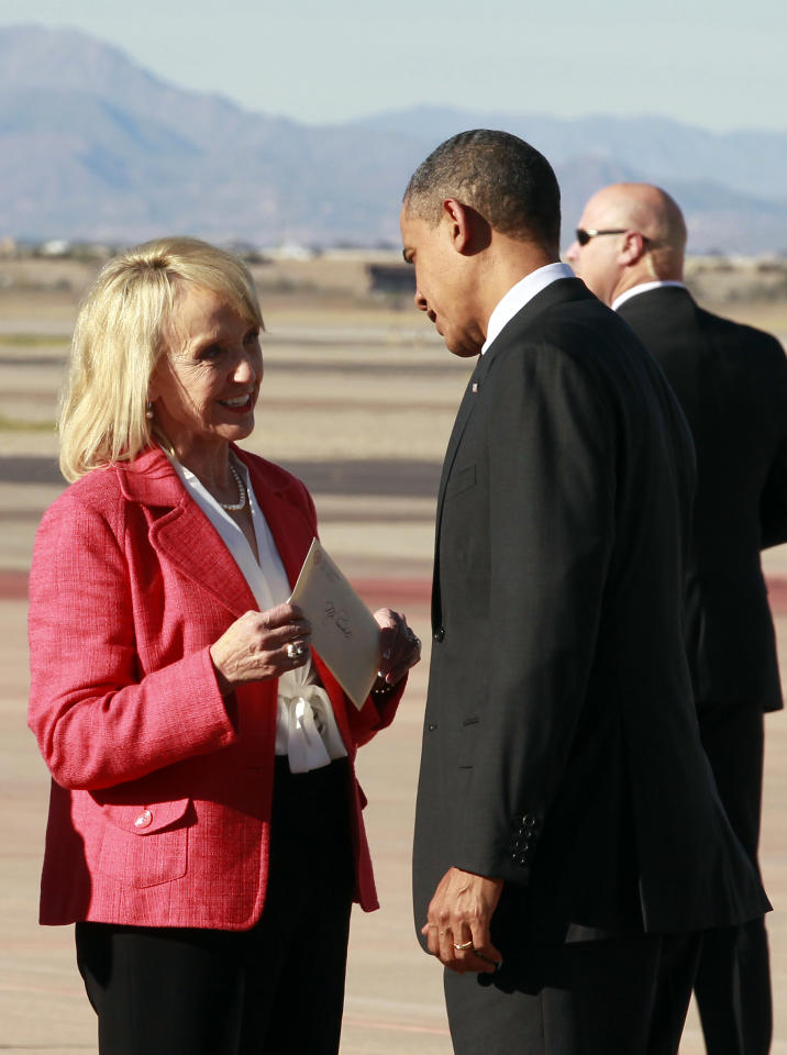 "President Barack Obama talks with Arizona Gov. Jan Brewer after arriving at Phoenix-Mesa Gateway Airport, Wednesday, Jan. 25, 2012, in Mesa, Ariz. Brewer greeted Obama and what she got was a book critique. Of her book. The two leaders engaged in an intense conversation at the base of Air Force One's steps. Both could be seen smiling, but speaking at the same time. Asked what the conversation was about, Brewer, a Republican, said: ""He was a little disturbed about my book."" Brewer recently published a book, ""Scorpions for Breakfast,"" something of a memoir that describes her years growing up and defends her signing of Arizona's controversial law cracking down on illegal immigrants, which Obama opposes. Brewer also handed Obama an envelope with a handwritten invitation for Obama to return to Arizona to meet her for lunch and to join her for a visit to the border. (AP Photo/Haraz N. Ghanbari)"