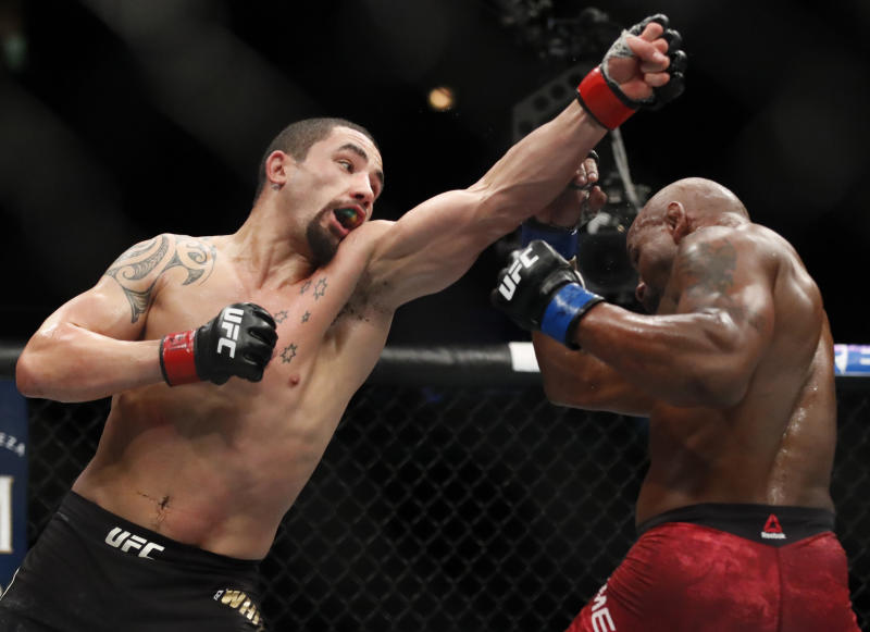 Robert Whittaker, left, won't fight at UFC 248. (AP Photo/Jim Young)