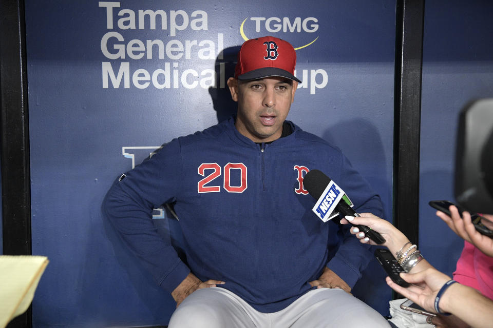 Boston Red Sox manager Alex Cora (20) answers questions from reporters in the dugout before a baseball game against the Tampa Bay Rays Friday, Sept. 20, 2019, in St. Petersburg, Fla. (AP Photo/Phelan M. Ebenhack)