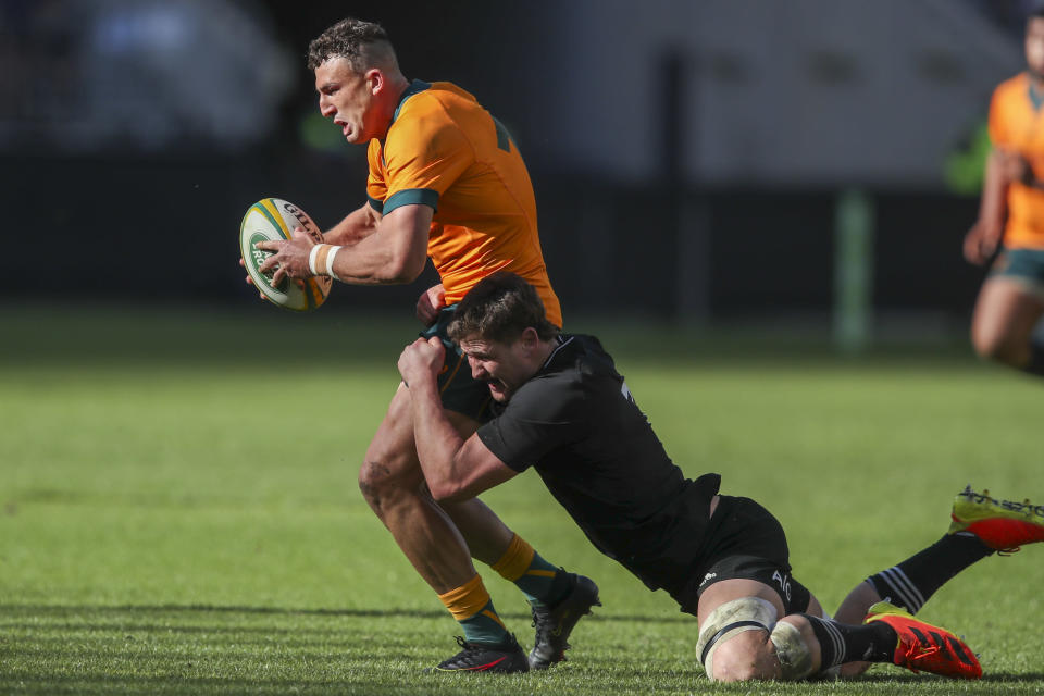 Australia's Tom Banks is tackled by New Zealand's Dalton Papalii during the Rugby Championship game between the All Blacks and the Wallabies in Perth, Australia, Sunday, Sept. 5, 2021. (AP Photo/Gary Day)