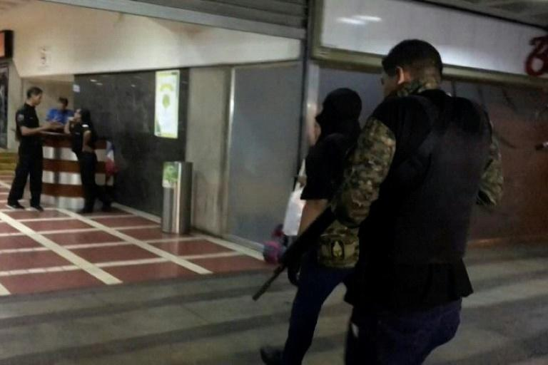 A video grab taken from AFP TV footage shows unidentified armed and hooded men walking into opposition leader Juan Guaido's party headquarters in Caracas, Venezuela