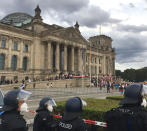 Police officers looks to protestors standing on the steps in front of the Reichstag building during a demonstration against the Corona measures in Berlin, Germany, Saturday, Aug. 29, 2020. (Lukas Dubro/dpa via AP)