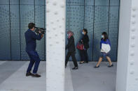 A cameraman takes images of people arriving at the court where relatives give testimony in the trial of four men charged with murder over the downing of Malaysia Airlines flight MH17, at Schiphol airport, near Amsterdam, Netherlands, Monday Sept. 6, 2021. Relatives of some of the 298 people killed in the downing of Malaysia Airlines flight MH17 tell a Dutch court about the impact on their lives of the disaster during the trial of three Russians and a Ukrainian charged with involvement in bringing down the Amsterdam-Kuala Lumpur flight more than seven years ago. (AP Photo/Peter Dejong)
