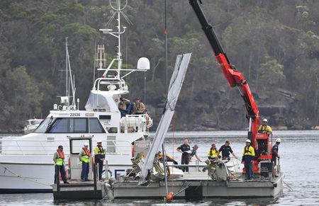 NSW police and salvage personnel work to recover the wreckage of the wing of the seaplane that crashed into Jerusalem Bay, north of Sydney, Australia, January 4, 2018. AAP/Mick Tsikas