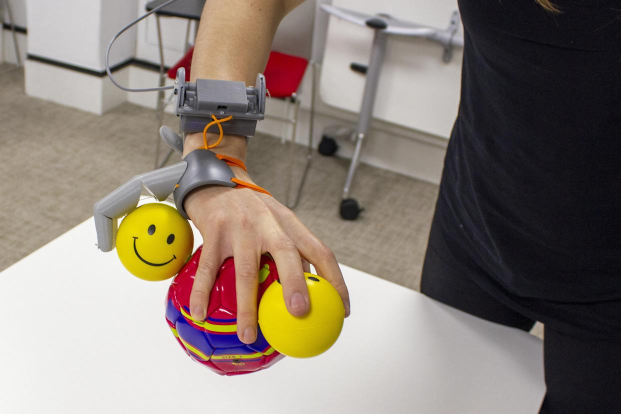 Participants used the 'Third Thumb' to complete training tasks including holding multiple balls with one hand. (SWNS)