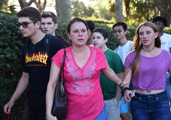 Students and adults leave following a shooting at Marjory Stoneman Douglas High School in Parkland, Florida.