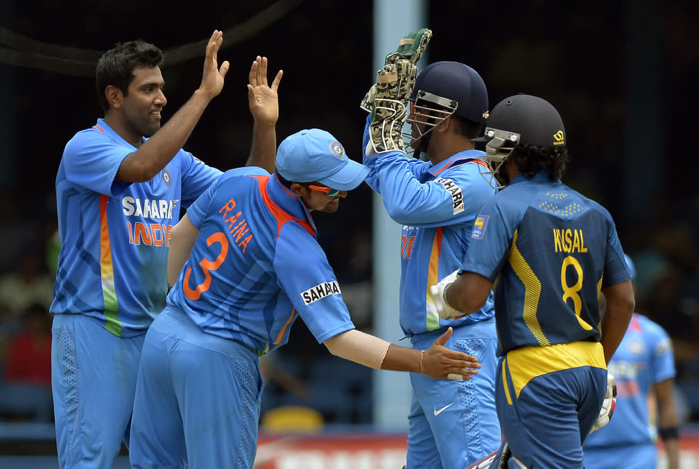 Indian cricketer Ravichandran Ashwin (L) celebrates with team captain Mahendra Sing Dhoni after dismissing Sri Lankan batsman Kusal Perera (R) during the final match of the Tri-Nation series between India and Sri Lanka at the Queen's Park Oval stadium in Port of Spain on July 11, 2013. India won the toss and elected to field first. AFP PHOTO/Jewel Samad