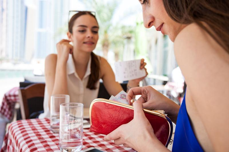 Two females paying for their meal. Source: Getty.