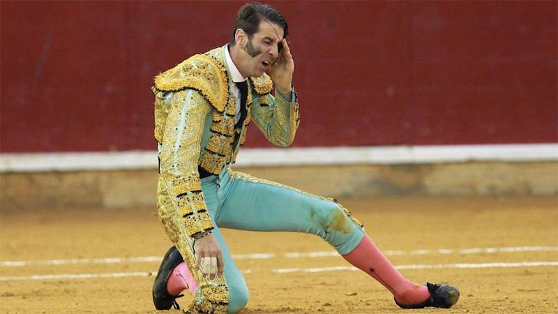 The bull struck the matador on the left side of his face and left the matador holding his left eye, wincing in pain. Photo: AFP