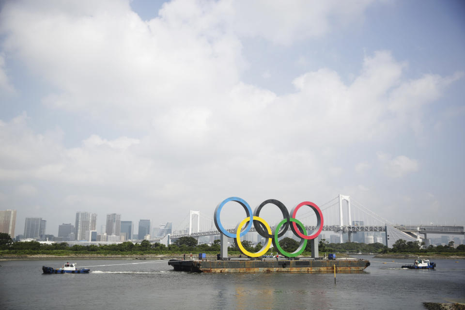 """Tugboats move a symbol installed for the Olympic and Paralympic Games Tokyo 2020 on a barge moved away from its usual spot off the Odaiba Marine Park in Tokyo Thursday, Aug. 6, 2020. The five Olympic rings floating on a barge in Tokyo Bay were removed for what is being called """"maintenance,"""" and officials says they will return to greet next year's Games. The Tokyo Olympics have been postponed for a year because of the coronavirus pandemic and are to open on July 23, 2021. The Paralympics follow on Aug. 24. (AP Photo/Hiro Komae)"""