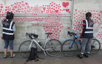 Women draw hearts on the 'The National COVID Memorial Wall' on the south bank of the Thames in front of St. Thomas' hospital and opposite the House of Parliament in London, Sunday April 4, 2021. Hearts are being drawn onto the wall in memory of the many thousands of people who have died in the UK from coronavirus, with organizers hoping to reach their target of 150,000 hearts by the middle of next week. (AP Photo/Tony Hicks)