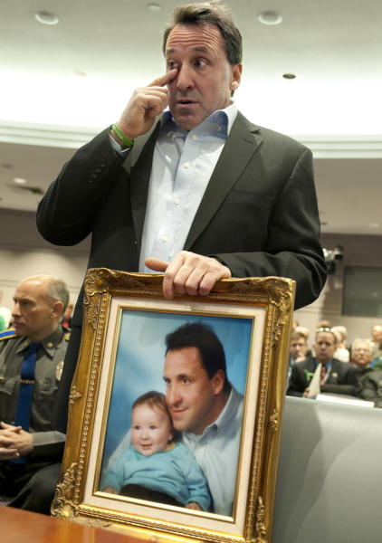 Neil Heslin, holding a picture of himself with his son Jesse, wipes his eye before testifying at a hearing in the Legislative Office Building in Hartford, Conn., Monday, Jan. 28, 2013. Heslin, whose 6-year-old son Jesse Lewis was one of the 20 first-graders killed in the Dec. 14 Newtown massacre, told a legislative subcommittee reviewing gun laws that there is no need for such weapons in homes or on the streets. (AP Photo/Jessica Hill)