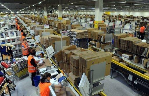 File picture taken on December 20, 2010 shows employees packing parcels at the Amazon logistics centre in Bad Hersfeld