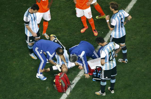 Argentina's Javier Mascherano receives help after a foul during the 2014 World Cup semi-finals between Argentina and the Netherlands at the Corinthians arena in Sao Paulo July 9, 2014. REUTERS/Fabrizio Bensch (BRAZIL - Tags: SOCCER SPORT WORLD CUP)