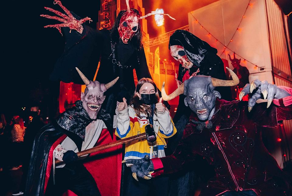 <p>Kaitlyn Dever is all good, posing next to a terrifying crew, during Halloween Horror Nights at Universal Studios Hollywood on Oct. 10.</p>