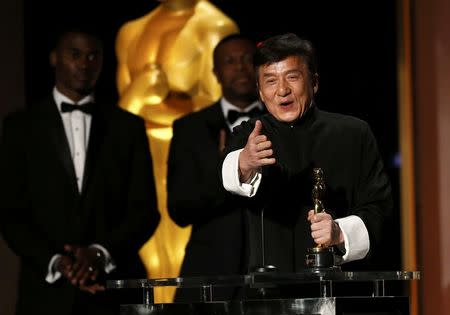 Actor Jackie Chan reacts as he accepts his Honorary Award as actor Chris Tucker (C) looks on at the 8th Annual Governors Awards in Los Angeles, California, U.S., November 12, 2016.   REUTERS/Mario Anzuoni