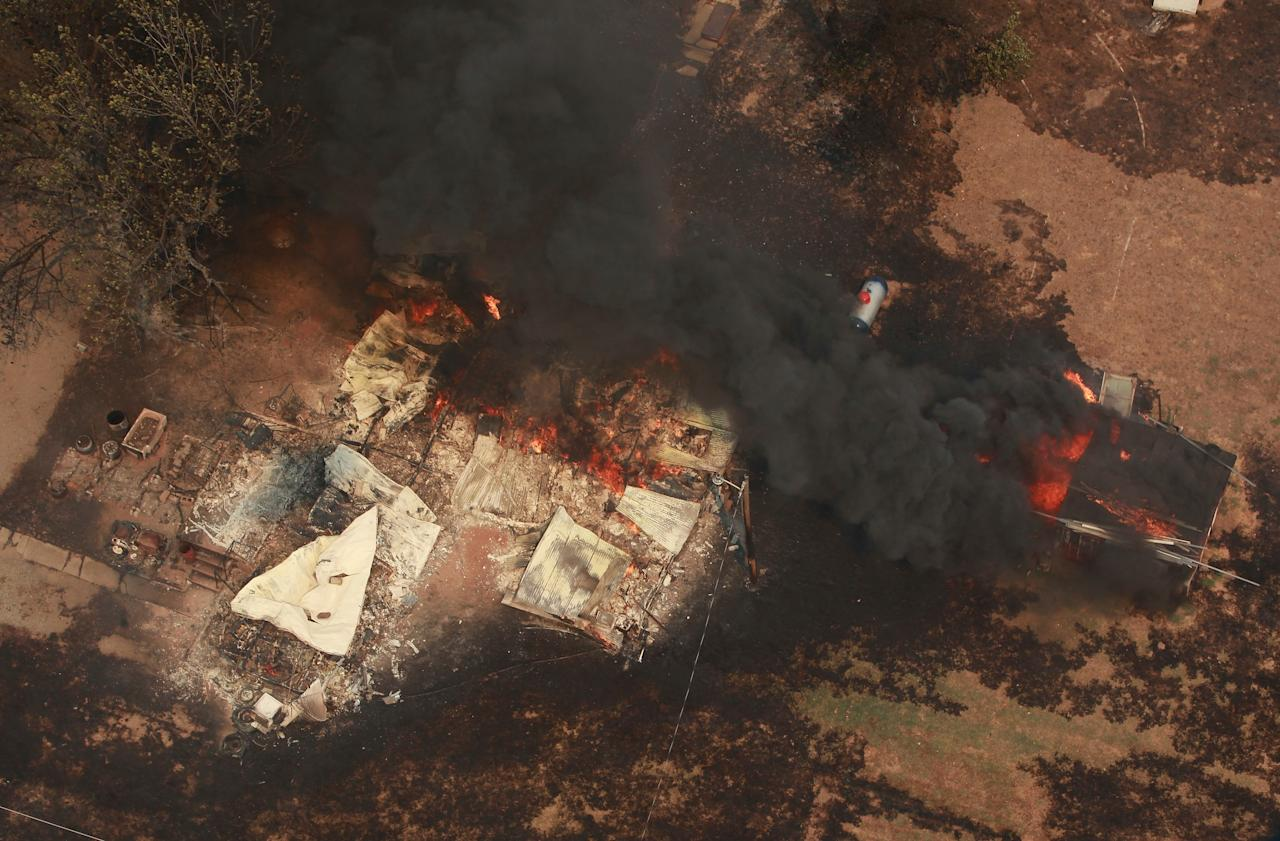 A house is engulfed in flames near Highway 48 and HW 38 junction east of Drumright, Okla., Saturday, Aug 4, 2012. While residents of one Oklahoma town sifted through their charred belongings Saturday to salvage what they could after a roaring wildfire that may have been deliberately set, residents in two other towns were being ordered to evacuate their homes. (AP Photo/Tulsa World Tom Gilbert)