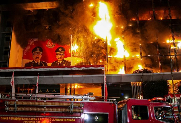 Firefighters douse a blaze at the attorney general's office in Jakarta