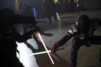 """In this Sunday, Feb. 10, 2019, photo, competitors battle during a national lightsaber tournament in Beaumont-sur-Oise, north of Paris. """"We wanted it to be safe, we wanted it to be umpired and, most of all, we wanted it to produce something visual that looks like the movies, because that is what people expect,"""" said Michel Ortiz, the tournament organizer. (AP Photo/Christophe Ena)"""