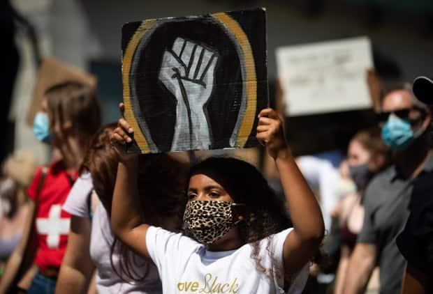 A young girl holds up a sign as she marches with hundreds of others on Emancipation Day in 2020. This year is the first time the day is officially marked by the federal government. (Darryl Dyck/The Canadian Press - image credit)