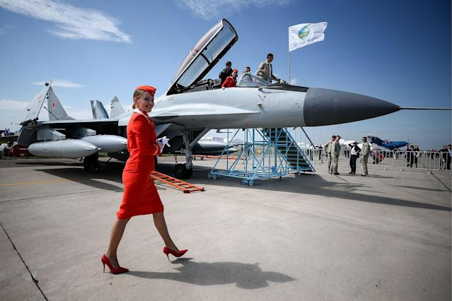 <p>An Aeroflot flight attendant walks by a Mikoyan MiG 29K fighter jet on display at the MAKS-2017 International Aviation and Space Salon in Zhukovsky, Moscow Region, Russia, July 18, 2017. (Photo: Sergei Bobylev/TASS via Getty Images) </p>
