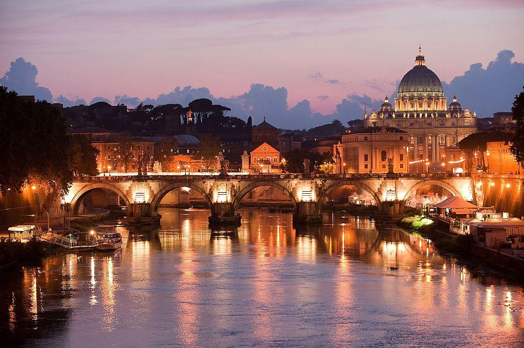 An overview of Saint Peter's basilica at the Vatican, from the Tiber river, at dusk in Rome, Italy. Every year around 15 milions of tourists are estimated to visit Rome.
