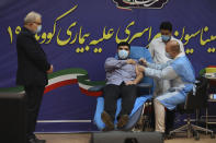 FILE— In this Feb. 9, 2021, file photo, Parsa Namaki, center, son of Health Minister Saeed Namaki, left, is injected with the Russian Sputnik V coronavirus vaccine in a staged event at Imam Khomeini hospital in Tehran, Iran, Iran. Iran has finalized a deal with Russia over purchasing 60 million doses Sputnik V Coronavirus vaccine, state-run IRNA news agency reported Thursday, April 15, 2021. (AP Photo/Vahid Salemi, File)