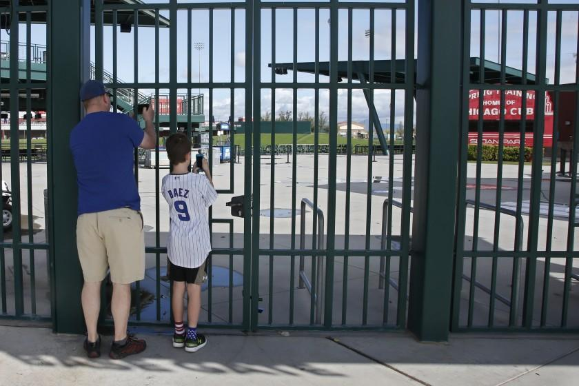 Fans take photos through the locked gates at the Cactus League's Sloan Park, the spring training site of the Chicago Cubs.