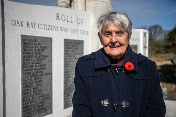 Anne Underhill stands in front of a memorial listing all the citizens of Oak Bay, B.C., who died in the Second World War, including her father, Robert Coventry. He's set to be memorialized with a plaque near the place where he died in England in 1940.