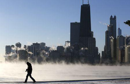 A man is silhouetted against the arctic sea smoke rising off Lake Michigan in Chicago