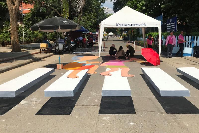 People paint a 3D pedestrian crossing in Kanchanaburi province