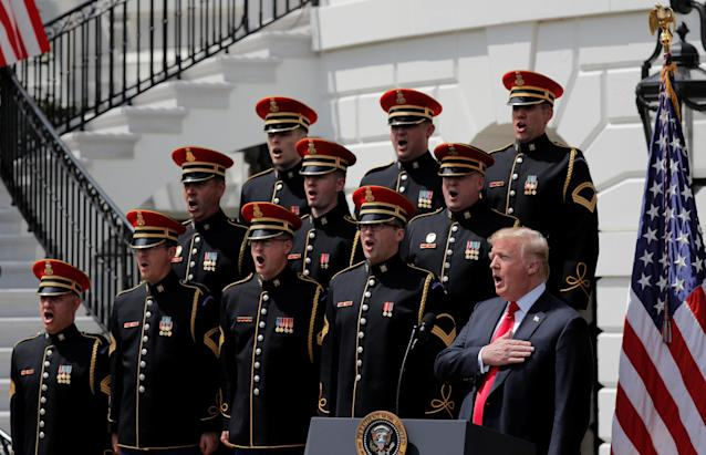 "U.S. President Donald Trump holds his hand over his heart and sings the U.S. National Anthem along with members of the United States Army Chorus at the ""celebration of America"" event on the South Lawn of the White House in Washington, U.S., June 5, 2018. The event was arranged after Trump canceled the planned visit of the Super Bowl champion Philadelphia Eagles to the White House. REUTERS/Kevin Lamarque"