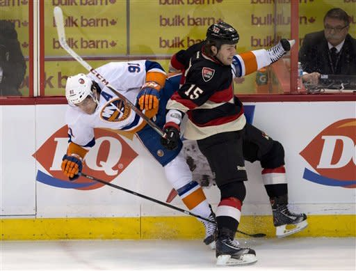 Ottawa Senators center Zack Smith collides with New York Islanders center John Tavares, left, along the boards during the first period of an NHL hockey game in Ottawa, Ontario, Tuesday, Feb. 19, 2013. (AP Photo/The Canadian Press, Adrian Wyld)