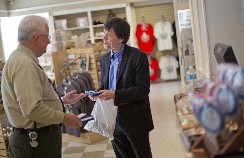 Documentary filmmaker Ken Burns, right, is presented with a Franklin D. Roosevelt commemorative coin by site manager Robin Glass after purchasing a t-shirt in the gift shop while visiting Roosevelt's Georgia home, Saturday, Nov. 2, 2013, in Warm Springs, Ga. Several members of the Roosevelt family toured the home known as the Little White House Saturday used by Roosevelt as Burns previewed parts of his 14-hour film on the Roosevelt's. (AP Photo/David Goldman)