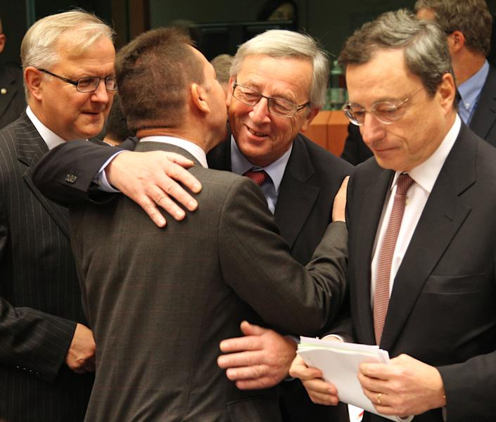 "Luxembourg's Prime Minister and chairman of the Eurogroup Jean-Claude Juncker, second right, greets Greek Finance Minister Yannis Stournaras, second left, as European Commissioner for Economic and Monetary Affairs Olli Rehn, left, and President of the European Central Bank Mario Draghi, right, look on, during the Eurogroup finance ministers meeting in Brussels, Monday, Nov, 12, 2012. Greece's international lenders have prepared a ""positive"" report on the country's reform efforts, a crucial step in its efforts to secure the next installment of its bailout loan, the head the of group of finance ministers from the 17 euro countries said Monday. (AP Photo/Yves Logghe)"