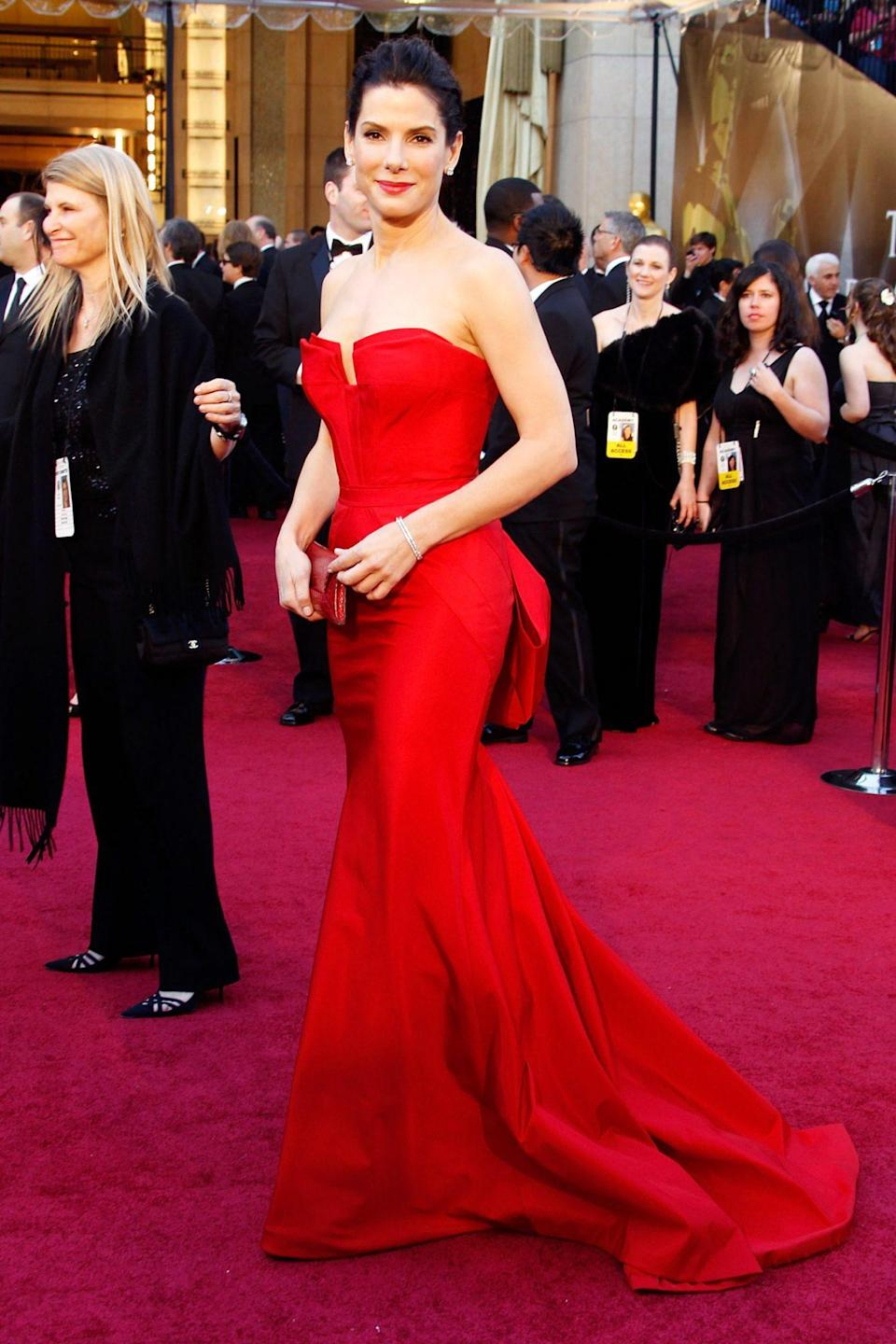 <p>Sandra Bullock — who had taken home her own Academy Award in 2010 for <em>The Blind Side</em> — looked red hot in Vera Wang.</p>