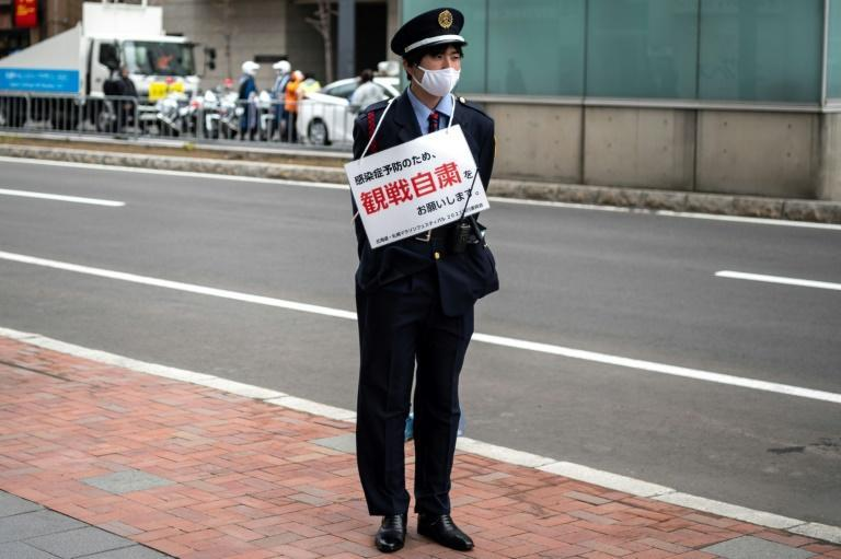 A security official wears a placard asking people not to watch the Olympic marathon test