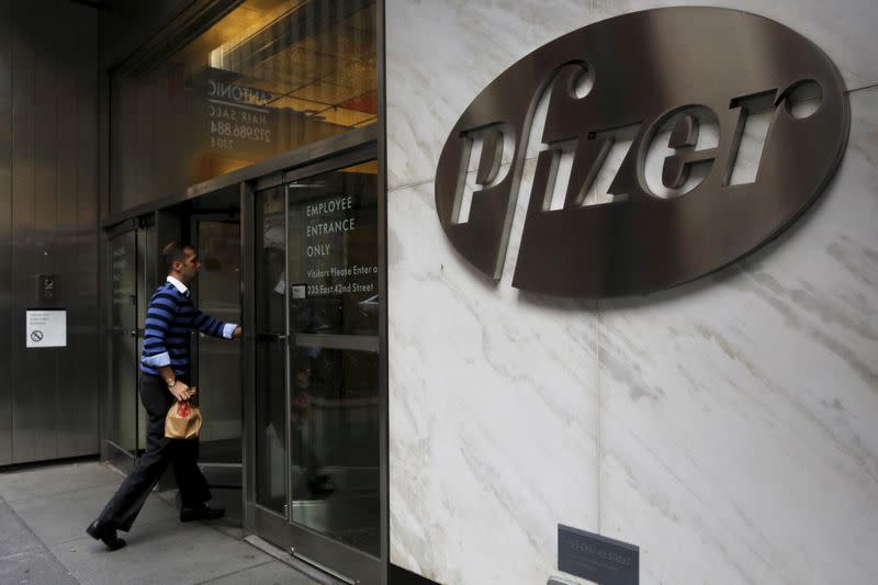 A man enters the employee entrance of the Pfizer World Headquarters building in New York