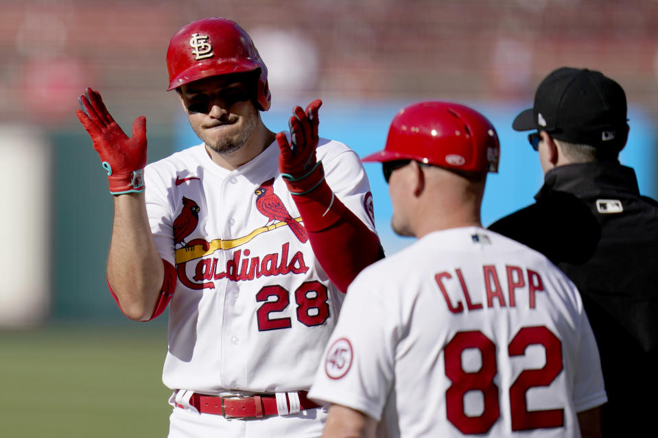 St. Louis Cardinals' Nolan Arenado (28) celebrates after hitting an RBI single as Cardinals first base coach Stubby Clapp (82) stands nearby during the third inning in the first game of a baseball doubleheader against the New York Mets Wednesday, May 5, 2021, in St. Louis. (AP Photo/Jeff Roberson)