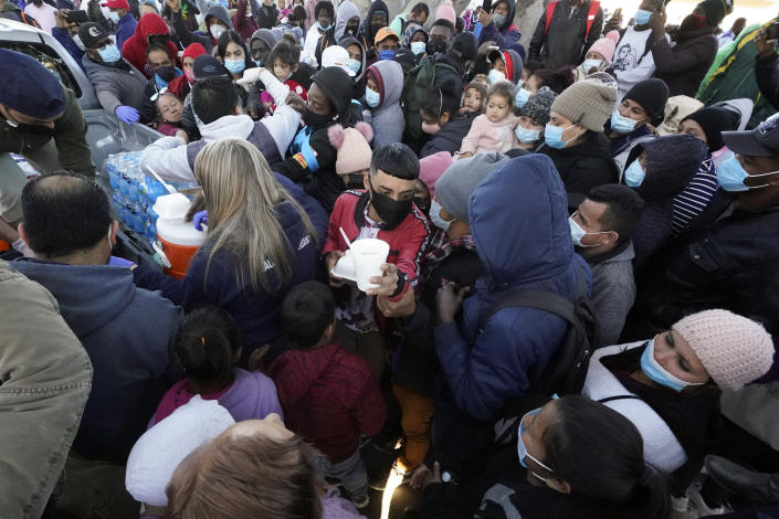 Asylum seekers receive food as they wait for news at the border, Friday, Feb. 19, 2021, in Tijuana, Mexico. After waiting months and sometimes years in Mexico, people seeking asylum in the United States are being allowed into the country starting Friday as they wait for courts to decide on their cases, unwinding one of the Trump administration's signature immigration policies that President Joe Biden vowed to end. (AP Photo/Gregory Bull)