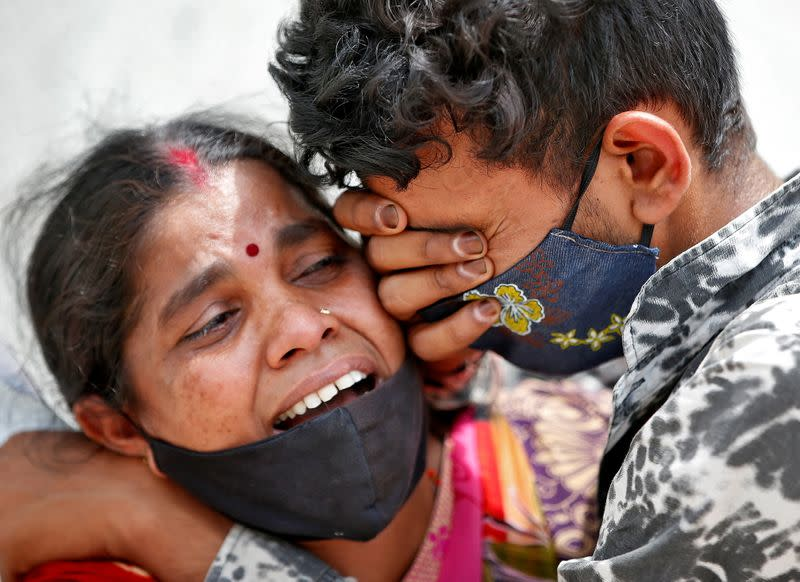 A woman mourns with her son after her husband died due to the coronavirus disease (COVID-19) outside a mortuary of a COVID-19 hospital in Ahmedabad