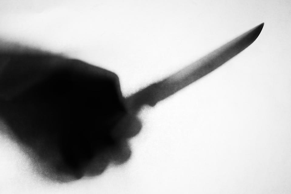 shadow of hand holding knife stabbing someone, soft focus, blurred