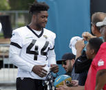 Jacksonville Jaguars middle linebacker Myles Jack (44) talks with fans and signs autographs before an NFL football practice at the teams training facility, Friday, July 26, 2019, in Jacksonville, Fla. (AP Photo/John Raoux)