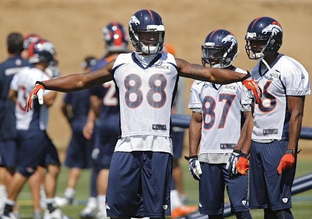 Denver Broncos wide receiver Demaryius Thomas (88) extends his arms as he talks to wide receiver Greg Hardin (87) and wide receiver Bennie Fowler, right, at the NFL football teams training facility in Englewood, Colo., on Tuesday, June 10, 2014. The Broncos opened their three-day mandatory minicamp on Tuesday.(AP Photo/Ed Andrieski)