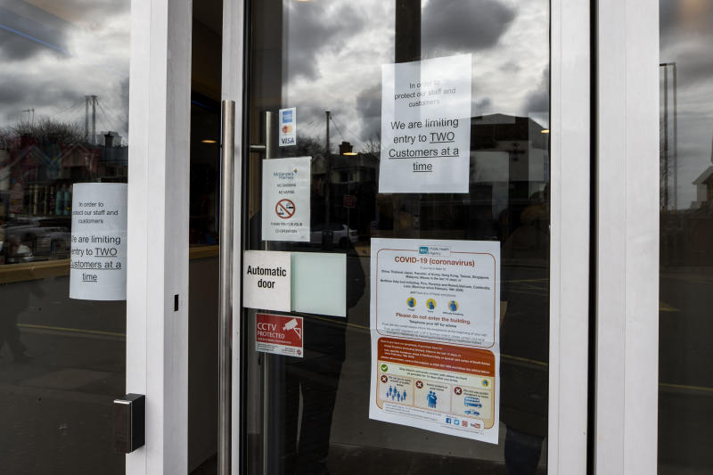 Signs on the door of McKenzie's Pharmacy on the Falls Road in Belfast limiting to two customers at any one time after they installed a post office style counter to protect staff and customers from Coronavirus. (Photo by Liam McBurney/PA Images via Getty Images)