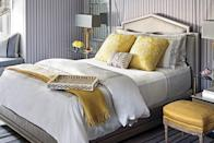 <p>Pops of sunny yellow and white steal the show in this inviting guest bedroom, which is outfitted in a striped wall covering.</p>
