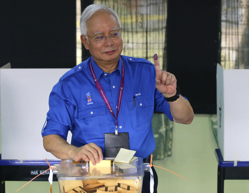 Then Malaysian Prime Minister Najib Razak looks at his finger marked with ink as he votes for the general election, at his hometown in Pekan, Pahang state, Malaysia, on Wednesday, May 9, 2018. Najib was found guilty Tuesday, July 28, 2020 in his first corruption trial linked to one of the world's biggest financial scandals - the billion-dollar looting of the 1MDB state investment fund. (AP Photo/Aaron Favila, File)