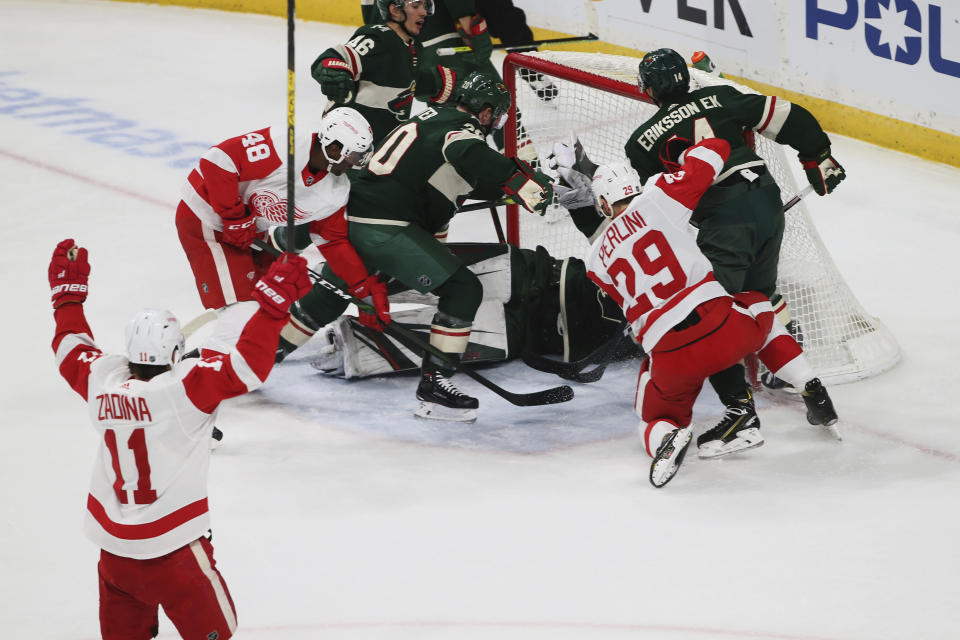 Detroit Red Wings' Filip Zadina, lower left, of Czech Republic, celebrates his power play goal off Minnesota Wild's Devan Dubnyk in the first period of an NHL hockey game Wednesday, Jan. 22, 2020, in St. Paul, Minn. It was Zadina's second goal of the period. (AP Photo/Jim Mone)